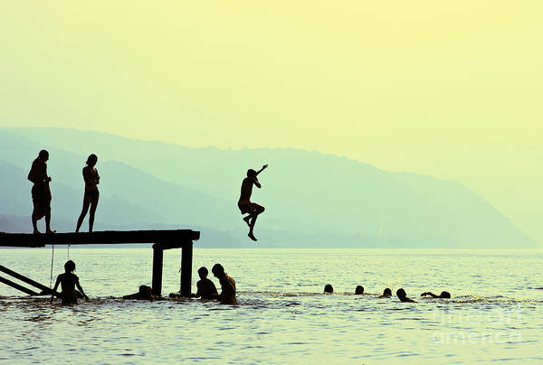 Wall Art - Photograph - Silhouettes Of Kids Who Jump Off Dock by Mita Stock Images