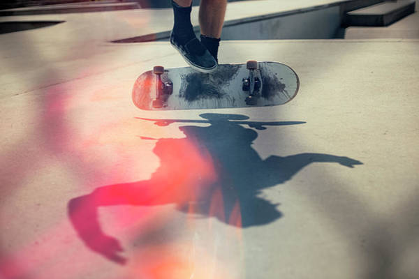 Sunlight Photograph - Skateboarder Doing An Ollie by Devon Strong