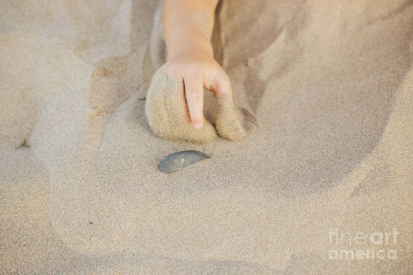 Photograph - Small Child's Hand Pointing A Stone With His Finger In The Sand Of The Beach by Joaquin Corbalan