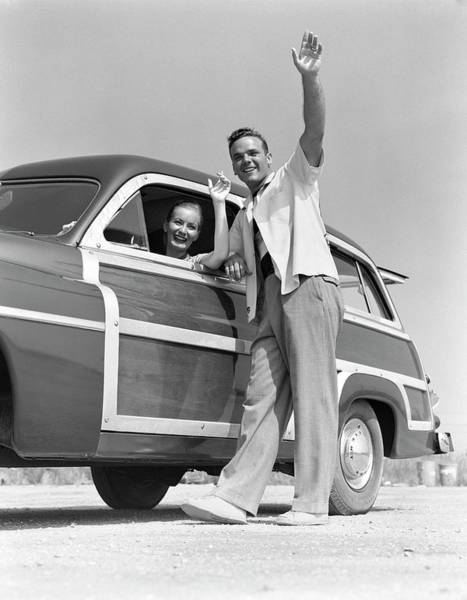 Heterosexual Couple Photograph - Smiling Couple Waving From A 1949 by H. Armstrong Roberts