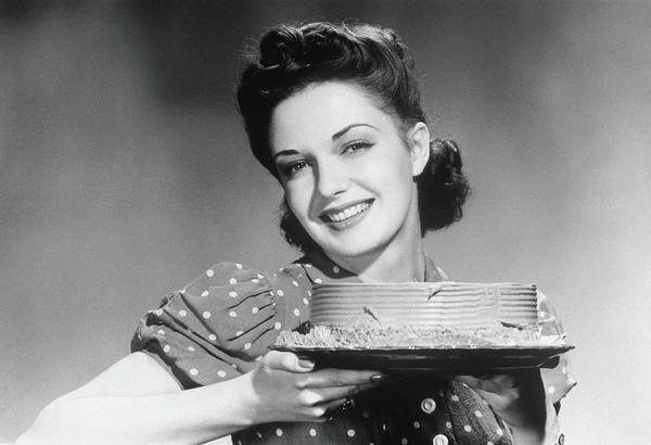 Caucasian Photograph - Smiling Woman Holding A Cake, 1945 by Archive Holdings Inc.