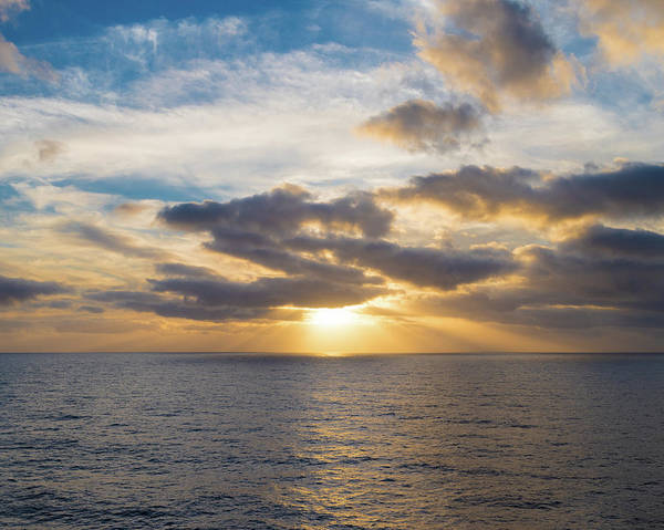 Photograph - Sun Shining Through Some Clouds Prior To Sunset At Sea by William Dickman