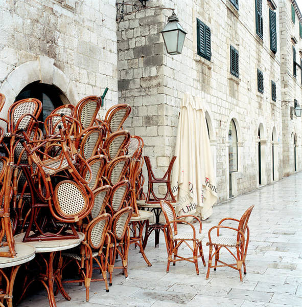 Photograph - Table And Chairs Stacked Against by Martin Puddy