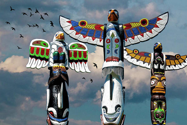 Photograph - Totem Poles Against A Cloudy Sky With Flying Birds by Randall Nyhof