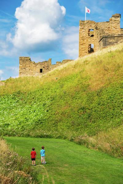 Sea Wall Art - Photograph - Two Boys With A Football Gaze Towards Tynemouth Priory And Castle by Iordanis Pallikaras