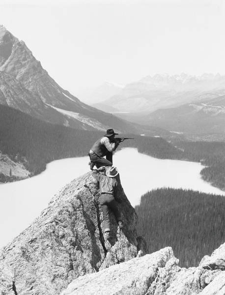 Canadian Culture Photograph - Two Cowboys On Top Of Rocky Crag, One by H. Armstrong Roberts