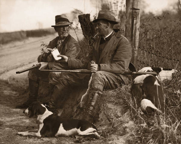 Gray Hair Photograph - Two Hunters With Dogs Sharing Cigars by Fpg