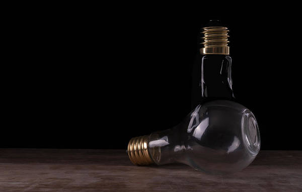 Photograph - Two Light Bulbs Arranged On A Wooden Table  by Vincent Billotto