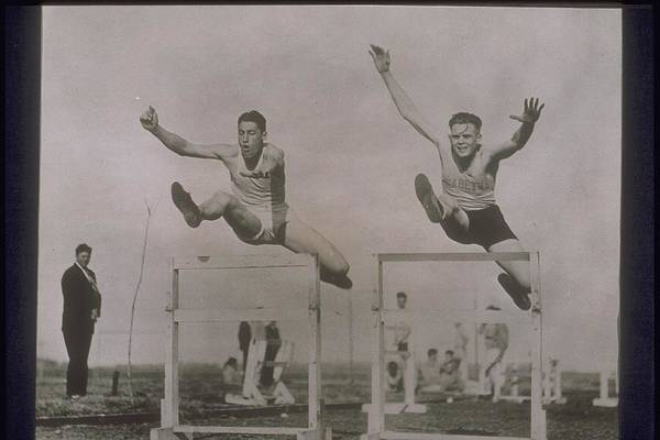 Caucasian Photograph - Two Male Hurdlers Leaping In Midair by Archive Holdings Inc.