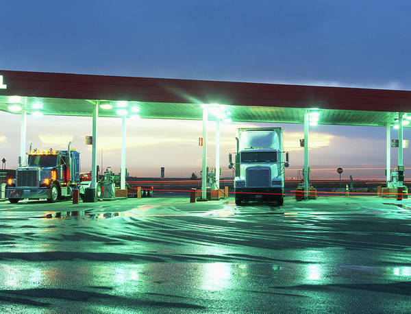 Semi Truck Photograph - Two Semi Trucks Parked At Gas Station by Brad Rickerby