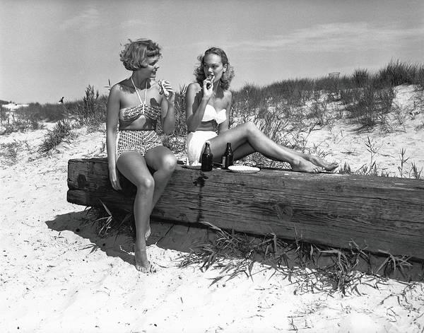 Bikini Photograph - Two Women In Bikini Eating Snack On by George Marks