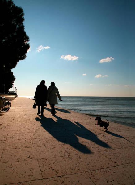 Friuli Photograph - Two Women Walking Dog Along Grado by Max Paoli