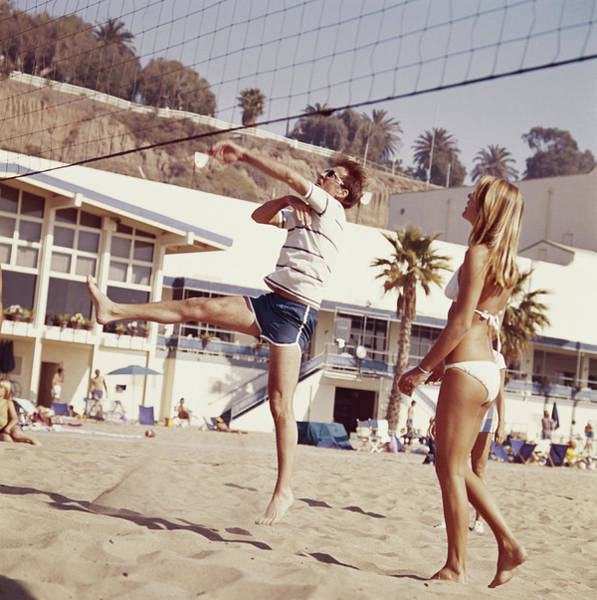 Bikini Photograph - Two Young People Playing Volleyball On by Tom Kelley Archive