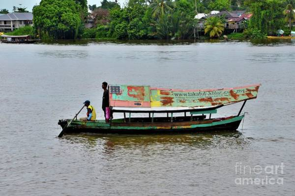 Photograph - Weathered Boat With Sailor And Passenger And Solar Panel Crosses Sarawak River Kuching Malaysia by Imran Ahmed