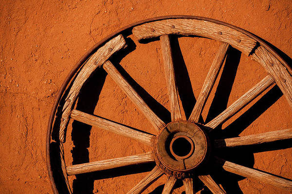 Wagon Wheel Photograph - Weathered Wagon Wheel Against An Adobe by Photo By Sam Scholes