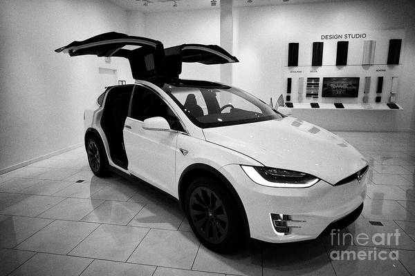 Wall Art - Photograph - white Tesla Model X with falcon wing doors open during celebration display in a tesla gallery showro by Joe Fox