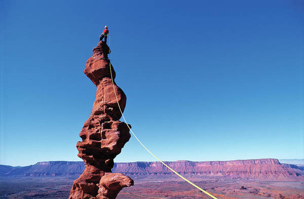 Climbing Photograph - Woman Balancing On Rock Tower In Utah by Simon Carter