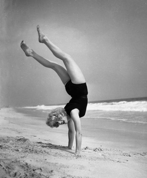 One Piece Swimsuit Photograph - Woman Does Handstand On The Beach B&w by Hulton Archive