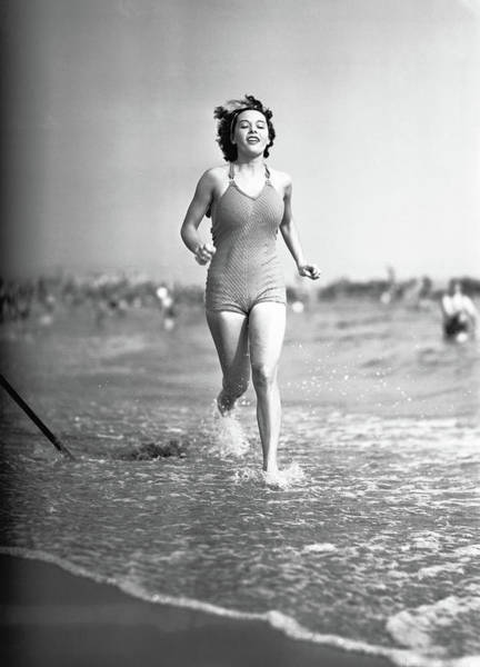 One Piece Swimsuit Photograph - Woman In Swimsuit Running On Shoreline by George Marks