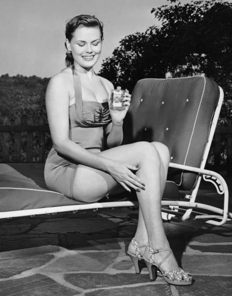 One Piece Swimsuit Photograph - Woman On Lawn Chair Applying Oil To Her by George Marks