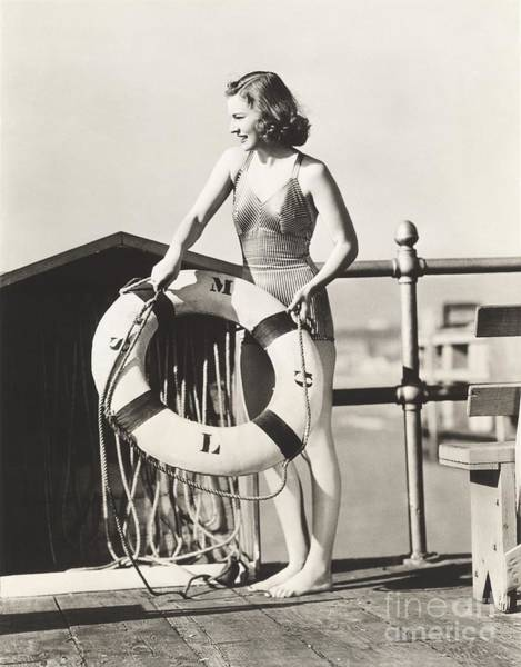 Bathing Suit Wall Art - Photograph - Woman On Pier Holding A Life Preserver by Everett Collection