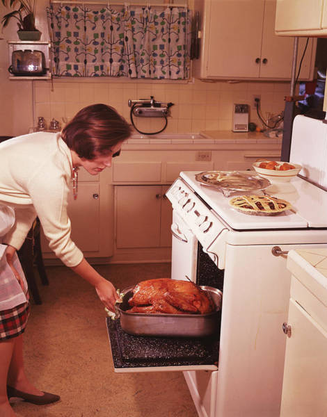 Caucasian Photograph - Woman Removes Cooked Turkey From Oven by Archive Holdings Inc.