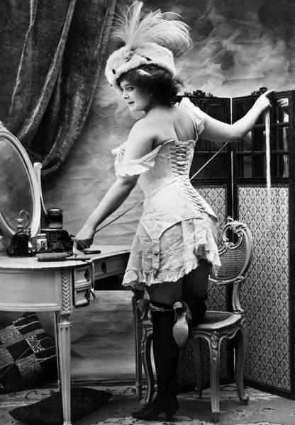 Photograph - Woman Tying Corset by Bettmann