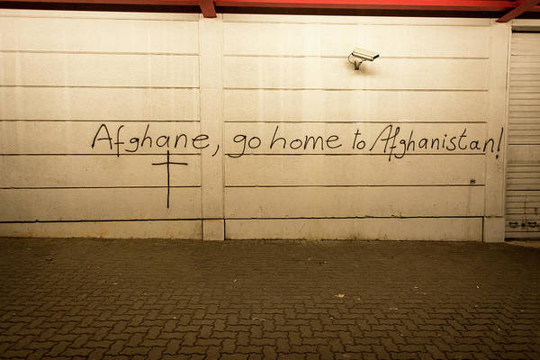 Wall Art - Photograph - Xenophobic Islamophobic Inscription Afghan Go Home To Afghanistan And Cross On A House Wall by imageBROKER - Stefan Haertel