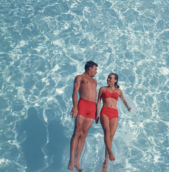 Wall Art - Photograph - Young Couple Jumping In Swimming Pool by Tom Kelley Archive