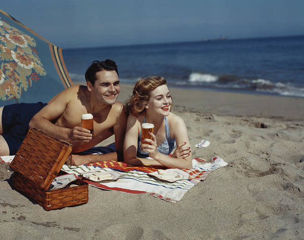 Archival Paper Photograph - Young Couple Lying On Beach With Beer by Tom Kelley Archive