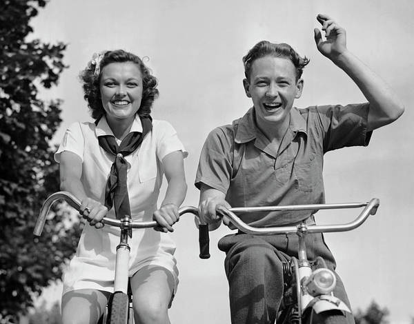 Heterosexual Couple Photograph - Young Couple Riding Bicycles by George Marks