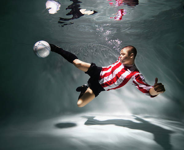 Underwater Photograph - Young Man Underwater Playing Football by Henrik Sorensen