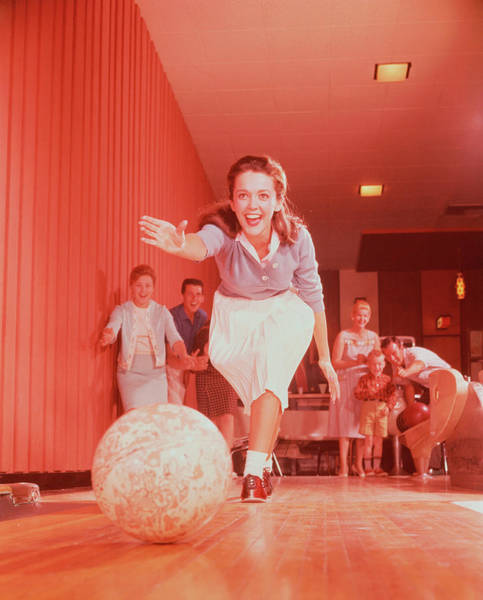 Ten Pin Bowling Wall Art - Photograph - Young Woman Bowling, Family Watching In by Fpg