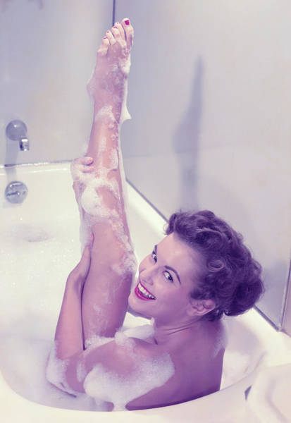 Young Woman In Bath Tub Lathering Art Print by Hulton Archive