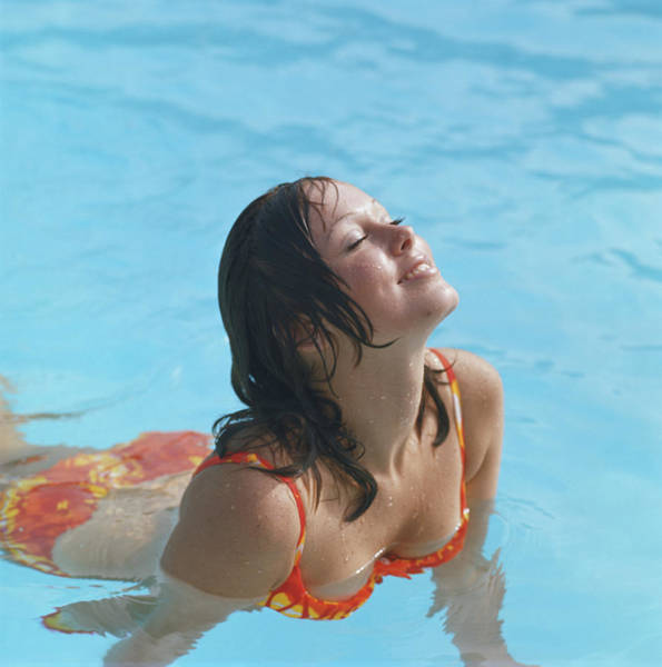 Toothy Smile Photograph - Young Woman In Bikini At Swimming Pool by Tom Kelley Archive