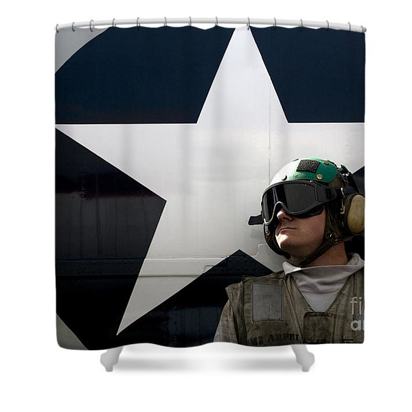 An Airman Stands In Front Of A C-2a Shower Curtain