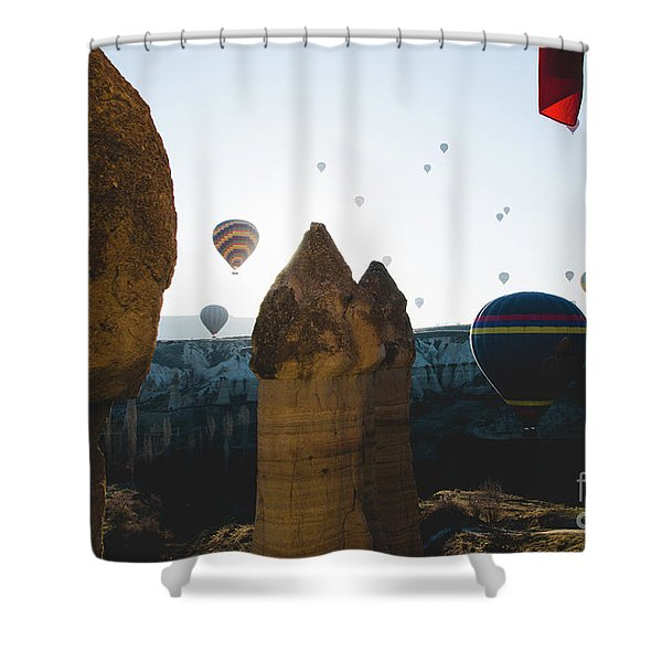 hot air balloons for tourists flying over rock formations at sunrise in the valley of Cappadocia. Shower Curtain