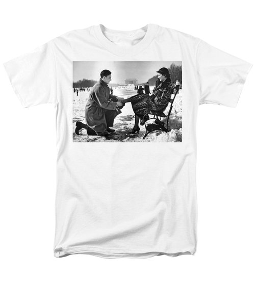 Man Lends A Helping Hand To Put On Skates Men's T-Shirt  (Regular Fit) by Underwood Archives