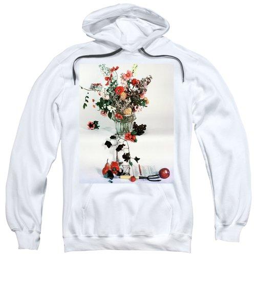 A Studio Shot Of A Vase Of Flowers And A Garden Sweatshirt