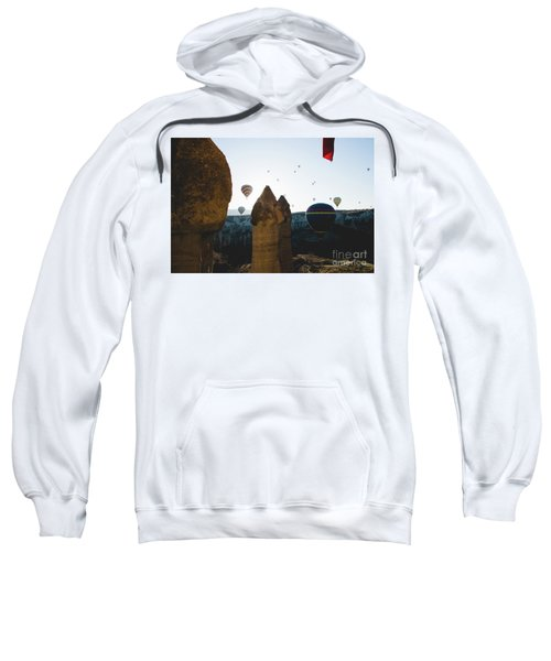 hot air balloons for tourists flying over rock formations at sunrise in the valley of Cappadocia. Sweatshirt
