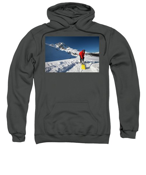 A Climber Shovels Snow In Order To Make Sweatshirt