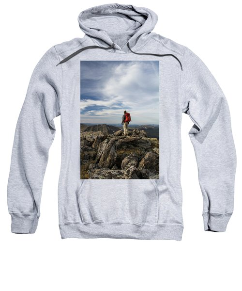 A Backpacker Stands Atop A Dramatic Sweatshirt