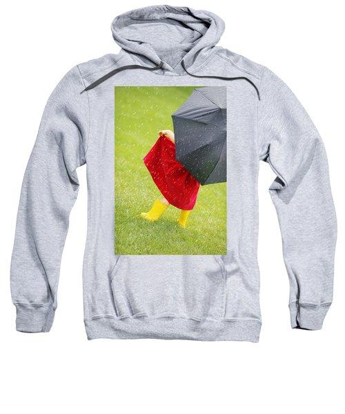 A Little Girl Walking In The Rain While Sweatshirt