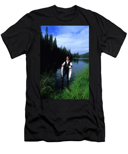 A Female Angler Holds Two Silver Coho Men's T-Shirt (Athletic Fit)