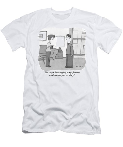 A Woman Stands In A Living Room Holding Men's T-Shirt (Athletic Fit)