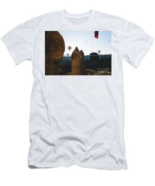 hot air balloons for tourists flying over rock formations at sunrise in the valley of Cappadocia. Men's T-Shirt (Athletic Fit)