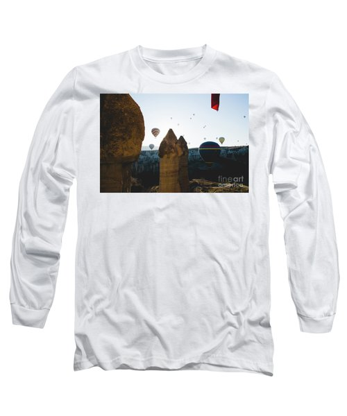 hot air balloons for tourists flying over rock formations at sunrise in the valley of Cappadocia. Long Sleeve T-Shirt