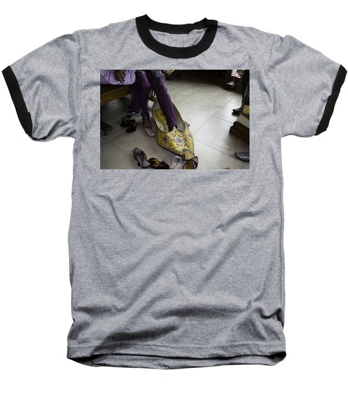 Trying On A Very Large Decorated Shoe Baseball T-Shirt by Ashish Agarwal