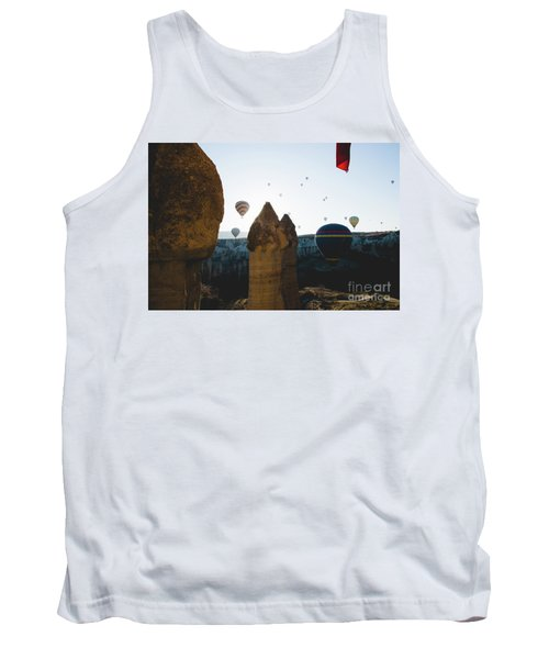 hot air balloons for tourists flying over rock formations at sunrise in the valley of Cappadocia. Tank Top