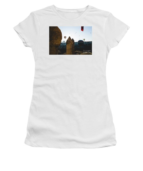 hot air balloons for tourists flying over rock formations at sunrise in the valley of Cappadocia. Women's T-Shirt